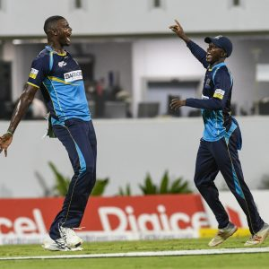 BRIDGETOWN, BARBADOS - SEPTEMBER 29: In this handout image provided by CPL T20, Jason Holder (L) and Hayden Walsh Jr. (R) of Barbados Tridents celebrate the dismissal of Andre Fletcher of St Lucia Zouks during match 26 of the Hero Caribbean Premier League between Barbados Tridents and St Lucia Zouks at Kensington Oval on September 29, 2019 in Bridgetown, Barbados. (Photo by Randy Brooks - CPL T20/Getty Images)